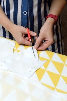 Le mani delle donne tagliano il tessuto con le forbici secondo il modello sul tavolo.