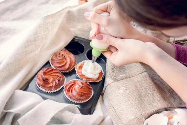 Le mani delle donne decorano i cupcakes con la crema