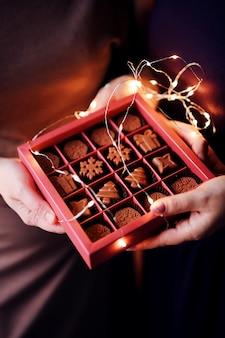 Le mani delle donne tengono una bella scatola di natale con cioccolatini fatti a mano a forma di fiocchi di neve