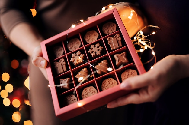 Le mani delle donne tengono una bella scatola di natale con cioccolatini al latte naturale fatti a mano a forma di fiocchi di neve