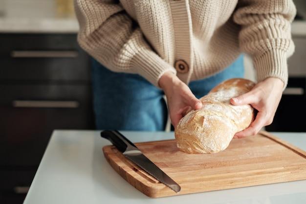 Le mani delle donne tengono il pane appena sfornato