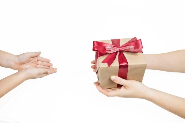 Le mani delle donne porgono una confezione regalo con un nastro rosso alle mani dei bambini su uno sfondo bianco Foto Premium
