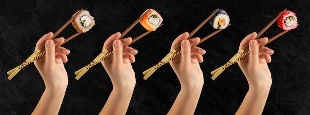 Le mani delle donne tengono i rotoli di sushi con i bastoncini. muro nero. concetto creativo.