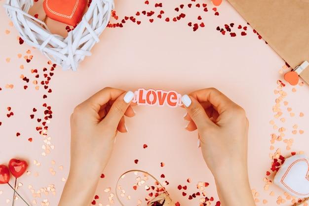 Le mani delle donne tengono la parola amoresfondo di san valentino con accessori per feste. san valentino concetto. vista dall'alto