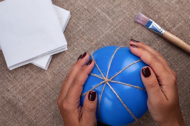 Le mani delle donne tengono un palloncino avvolto in una corda di iuta, il processo di creazione di una zucca di cartapesta,