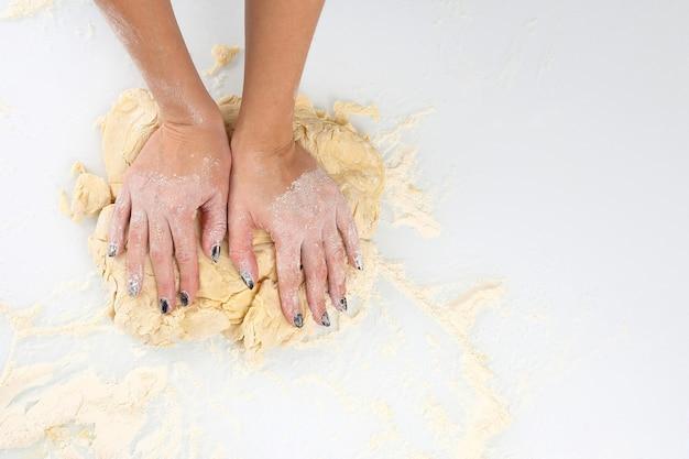 Le mani delle donne impastano la pasta su una luce