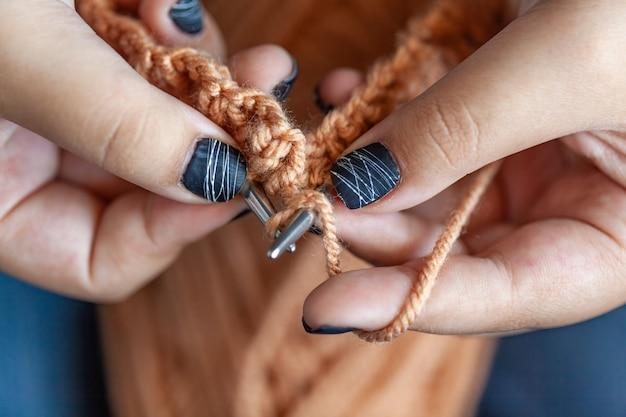 Le mani delle donne sono lavorate a maglia in lana colorata. maglieria a mano