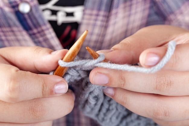Le mani delle donne sono lavorate a maglia in lana grigia