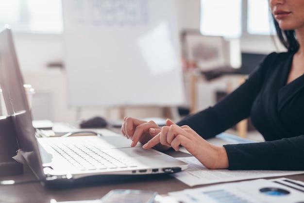 Le mani delle donne sulla tastiera di un computer portatile in primo piano.
