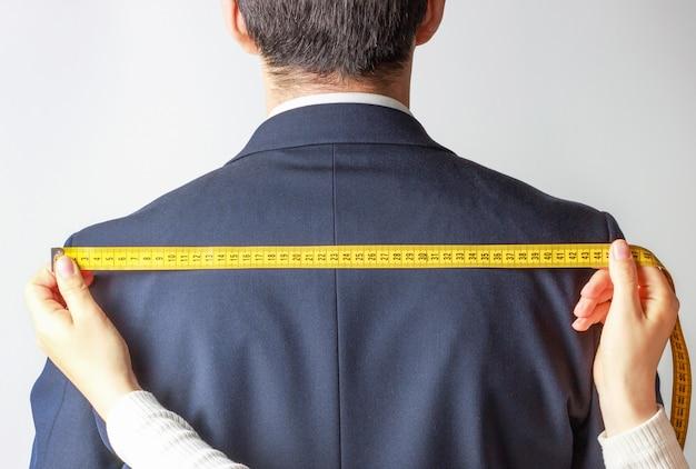 Le mani delle donne misurano la giacca con cintura santiment su bianco, vista posteriore