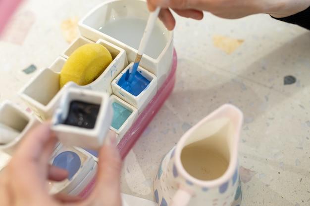 Le mani delle donne mescolano la vernice per colorare una brocca di latte in ceramica in officina.