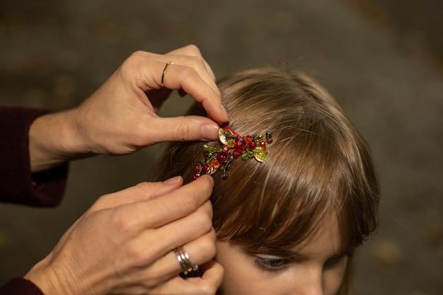 Le mani delle donne di una madre o di una badante fissano con cura una molletta sui capelli di una bambina.
