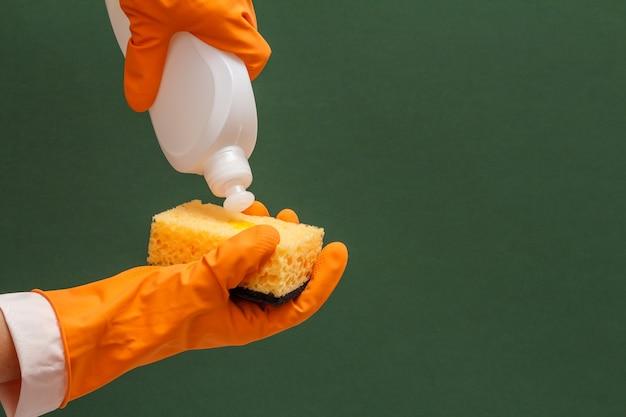 Le mani delle donne in guanto protettivo arancione con bottiglia di detersivo per piatti e spugna sullo sfondo verde. concetto di lavaggio e pulizia.