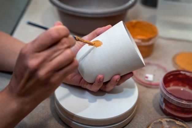 Mani di donna che dipingono un oggetto in ceramica
