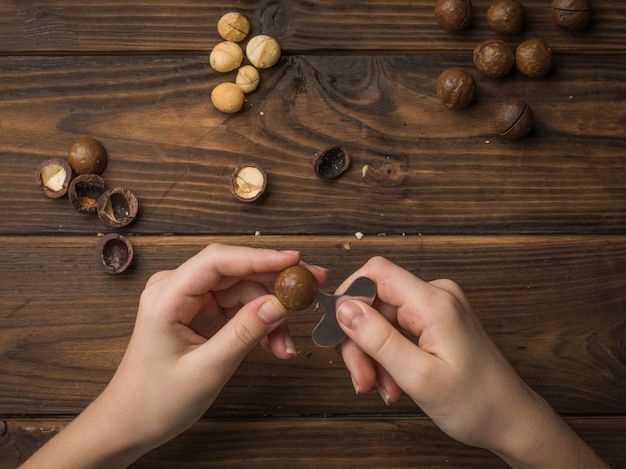 Le mani delle donne sbucciano le noci di macadamia dai loro gusci su un tavolo di legno. superfood.