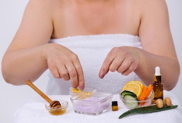 Le mani delle donne preparano una maschera per il viso e il corpo con prodotti naturali a casa e distoglie lo sguardo. cura della pelle domestica. foto di alta qualità