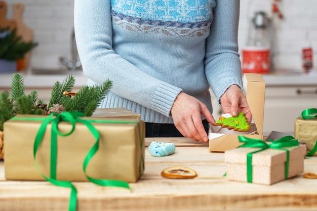 Le mani delle donne mettono i biscotti in una scatola