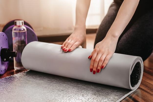 Le mani delle donne arrotolano un materassino yoga. sport a casa. la donna piega la stuoia di yoga dopo lo sport. avvicinamento