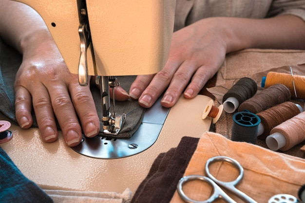 Le mani delle donne cuciono su una macchina da cucire sullo sfondo di tessuti e fili.