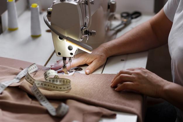 Mani delle donne e sarta della macchina da cucire