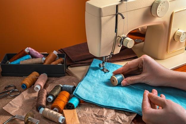 Mani delle donne, filo e macchina da cucire su fondo in terracotta.