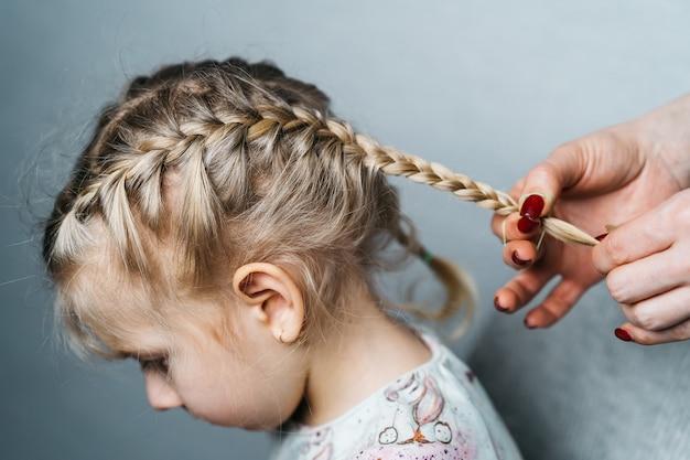 Le mani delle donne intrecciano trecce per una bambina, acconciature per bambini a casa, una spighetta di capelli.