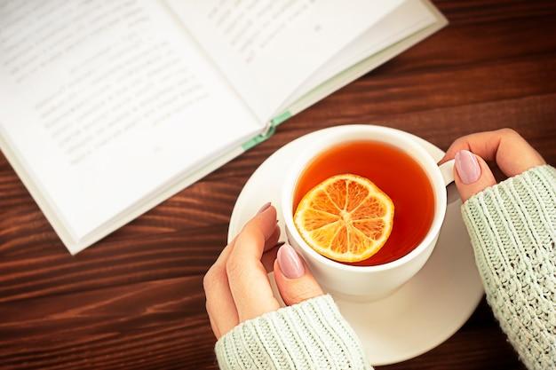 Mani delle donne con una tazza di tè e un libro