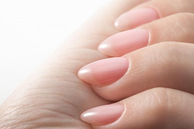 Mani da donna con perfetta manicure nude.