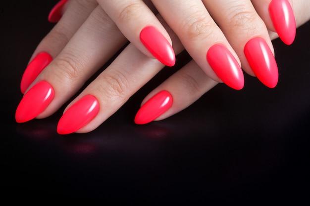 Mani femminili con perfetta manicure rossa. smalto color corallo rosso.