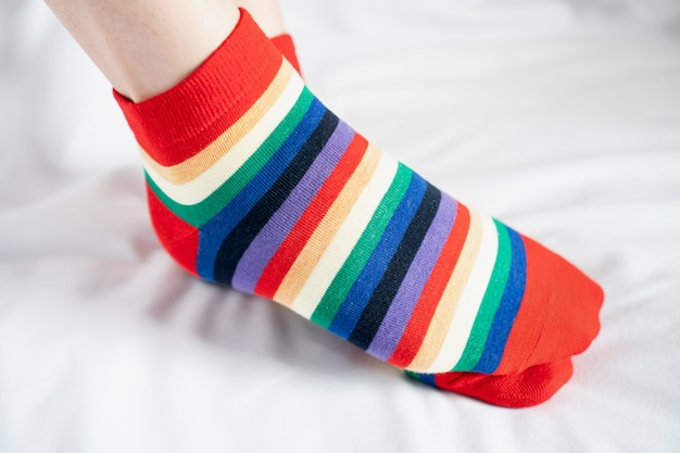Gambe da donna in calzini vari colori alternati, piedistallo sul pavimento in tessuto bianco.