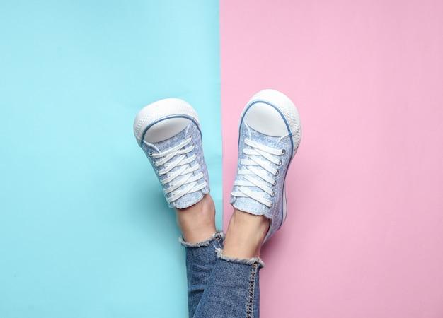 Gambe da donna in jeans attillati e strappati, scarpe da ginnastica in rosa pastello blu. vista dall'alto