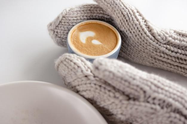 Le mani guantate delle donne tengono una tazza di caffè su una fine bianca del tavolo su