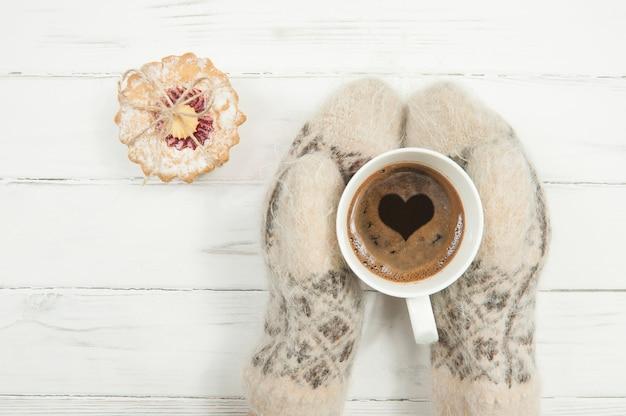 Le mani guantate delle donne tengono una tazza di caffè con un cuore e una torta accanto su una fine bianca del tavolo in legno