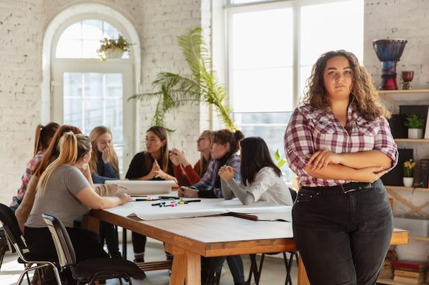 Diritti e uguaglianza delle donne in ufficio. donne d'affari caucasiche o giovani modelle sicure hanno incrociato le mani davanti ai colleghi che si sono incontrati per problemi sul posto di lavoro, pressione maschile e molestie.
