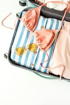 Costume da bagno bikini estivo da donna, occhiali da sole alla moda e vestito in valigia
