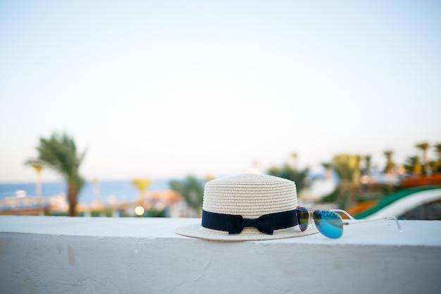 Cappello e occhiali estivi da donna giacciono sulla terrazza con vista sul mare