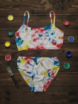 Biancheria intima da donna dipinta in stile tie dye e un set di colori su un tavolo di legno scuro.