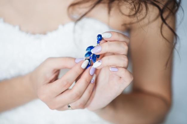 I gioielli di nozze delle donne (orecchini) nelle mani della sposa, fuoco selettivo