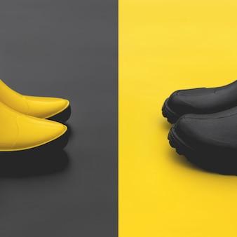 Stivali da donna in gomma gialla su sfondo nero e stivali da uomo in gomma nera su uno sfondo giallo si trovano uno di fronte all'altro.