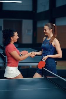 Le donne si stringono la mano prima della partita di ping pong, i giocatori di ping pong