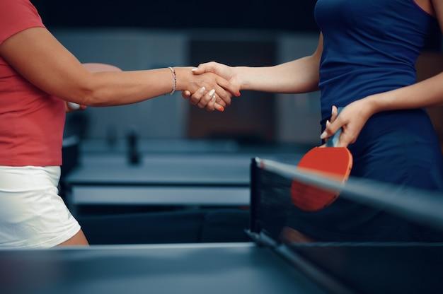 Le donne si stringono la mano prima della partita di tennis da tavolo