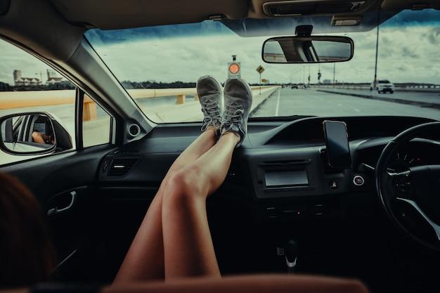 Donne sedute sul sedile del passeggero in auto con i piedi sul cruscotto dell'auto. giovane donna che si rilassa in macchina. durante le vacanze estive. concetto di viaggio.