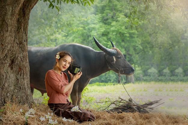 Donne sedute sotto un albero contro i bufali nei campi rurali