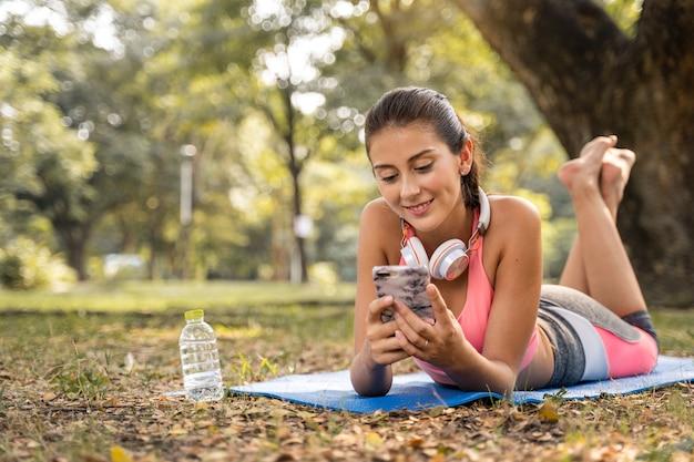 Donne sedute con sorridenti felici e ascoltando la musica nel parco per rilassarsi