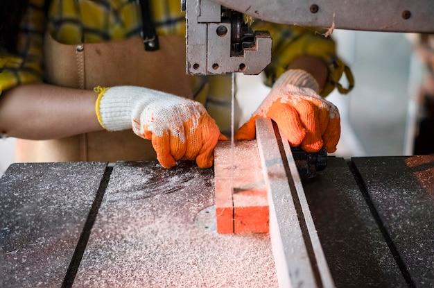 Le donne in piedi stanno lavorando artigianalmente il legno tagliato su un banco di lavoro con seghe a nastro utensili elettrici