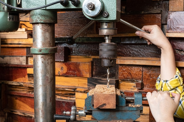 Le donne in piedi stanno lavorando artigianalmente il legno del trapano su un banco di lavoro con utensili elettrici drill press