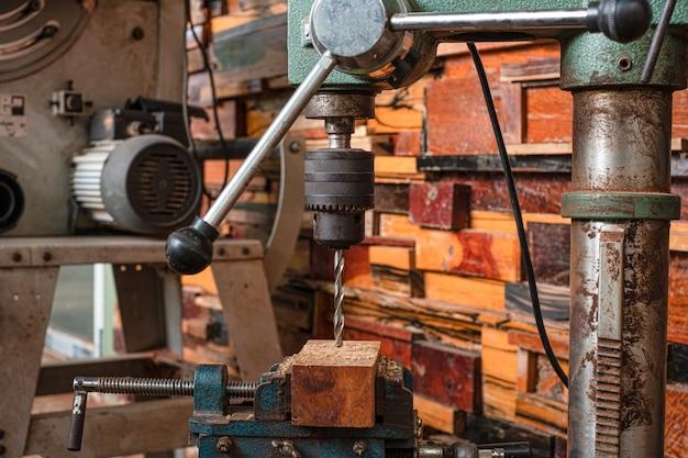 Le donne in piedi stanno lavorando artigianalmente il legno del trapano su un banco da lavoro con utensili elettrici drill press