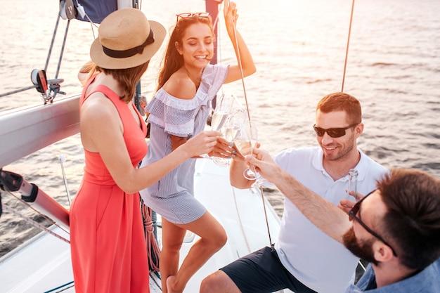 Le donne stanno di fronte agli uomini. tutti tengono bicchieri di champagne