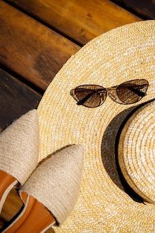 Cappello estivo da donna, occhiali da sole e scarpe da muli giacciono su uno sfondo di legno. posto per un'iscrizione o una pubblicità