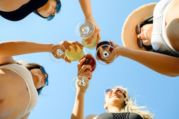 Donne in costume da bagno tintinnano bicchieri con cocktail freschi, vista dal basso, festa in piscina all'aperto. belle ragazze si rilassano a bordo piscina in una giornata di sole, vacanze estive di amiche attraenti